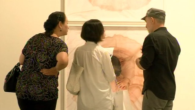 Visitors look at a painting of a flower at a Singapore art show