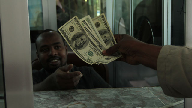 Money being handed over in US dollars at Dahashiil money transfer centre in Hargeisa. Photo by Jacques Sweeney