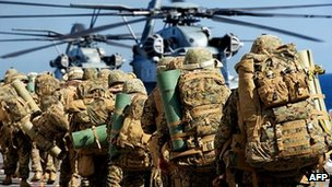 US Marines march to board two board helicopters aboard the USS Wasp during Bold Alligator