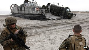 Marines watch over a Navy landing craft as it is unloaded during Bold Alligator