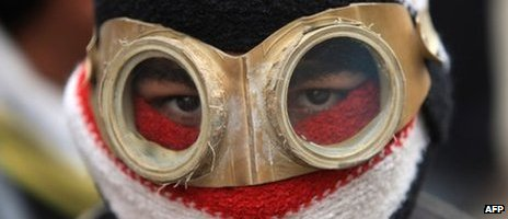 A masked Egyptian protester is seen during clashes with riot police near the interior ministry in the capital Cairo on 6 February 2012, as one protester was killed in the wake of deadly football violence and amid calls by activists for civil disobedience in Egypt.