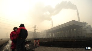 Two people talking outside coal-fired power plant in Linfen, Shanxi province.