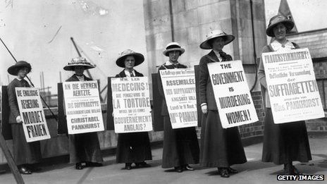 A group of suffragette women demonstrating with placards, in English, French and German, condemn the British government
