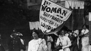 A protest march by women suffragettes in London with police in attendance. The banner held by the leading women reads '1st Woman Suffragist Arrested in London'