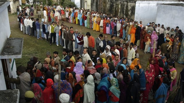 Voters queue outside a polling station in Uttar Pradesh