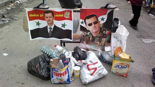 Pictures of Syria's President Bashar al-Assad are placed in the middle of a street among trash in Bab Sabaa neighbourhood of Homs