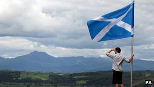 man next to saltire overlooking hills