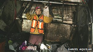 A rubbish collector stands inside the truck
