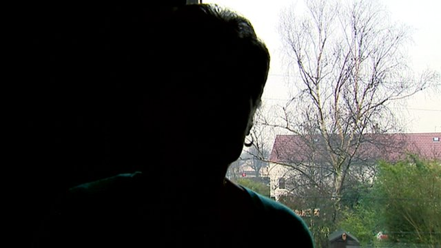 Silhouette of a woman sitting by a window