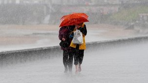 People share an umbrella on Whitley Bay, Yorkshire, during the wettest August in Britain on record, 2008