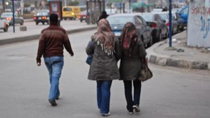 Asmaa and Sahaar walk away from the camera on a Cairo street