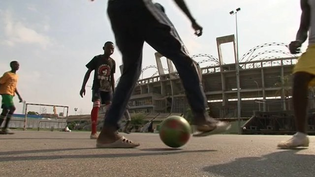 Teenagers play football outside an unfinished stadium