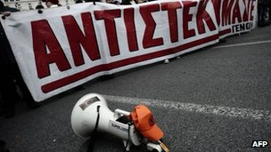"A megaphone lies in the road in Athens beside protesters with a banner reading  ""We resist"", 9 February"