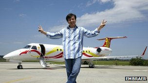 Jackie Chan in front of his Embraer jet
