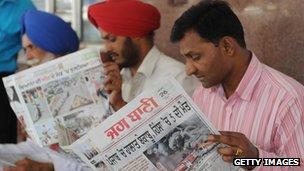 Indian men read newspapers