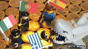 Lego shark eating lego men holding Greek, Italian, Portuguese and Spanish flags, on a floor of euro coins