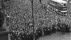 circa 1930: A huge crowd in Mare Street, Hackney, London, watches firemen putting out a blaze at the premises of Messrs Polikoff Ltd