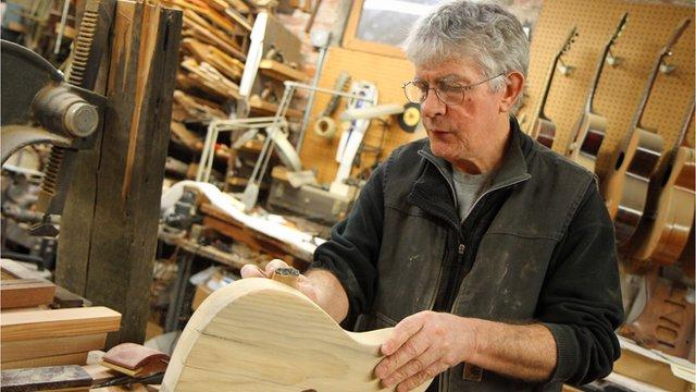 Guitar maker sanding unfinished guitar