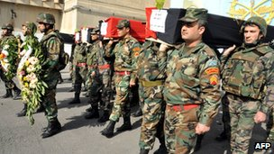 Syrian soldiers carry the coffins of security forces personnel killed in Damascus (9 February 2012)