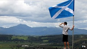 A man holds Scotland's flag aloft as he looks out over the Carse of Stirling