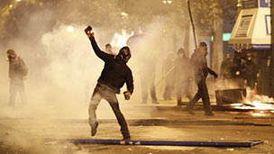 A protester throws an object at police in Athens. Photo: 12 February 2012