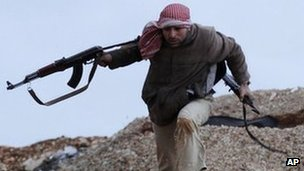 Syrian rebel fighter runs for cover in Idlib. 8 Feb 2012