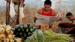 Suliban Molina, centre, reads state-run newspaper Granma as he waits for customers at a food market in Havana, Cuba, 27 January 2012