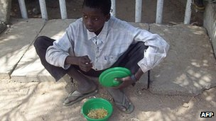 A child beggar receives food in Kano, Nigeria (Archive shot)
