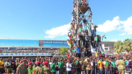 Thousands of Zambian people gather at Lusaka airport, some climbing on to a scaffold to get a glimpse of the football players