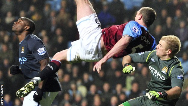 Richard Dunne goes flying after a challenge with Manchester City goalkeeper Joe Hart