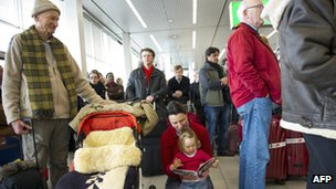Passengers wait at Schiphol airport
