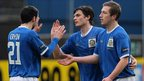 Jim Ervin and Mark McAllister congratulate Linfield goalscorer Philip Lowry at Windsor Park
