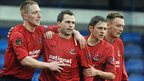 Crusaders players congratulate David Rainey after he scores their third goal against Glenavon