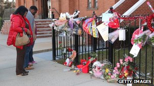 People view a makeshift memorial outside The New Hope Baptist Church in Newark, New Jersey 13 February 2012