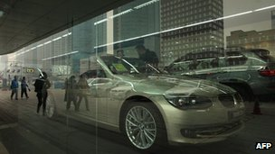 Pedestrians reflected in the window of a BMW car dealership in Beijing