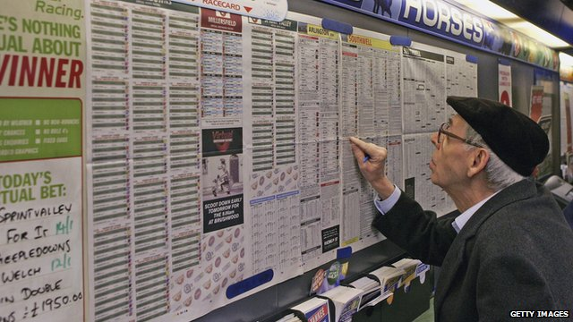 Man looking at horses in a betting shop