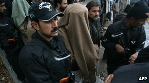 Pakistani policemen escorts one of the seven men at the Supreme Court in Islamabad on Monday