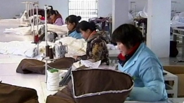 Chinese workers sewing winter products