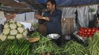 A customer buys vegetables from a street side vendor in Mumbai, India
