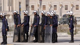 A line of riot police in front of razor wire near a shopping mall and cinema in Manama, Bahrain on 14 February 2012