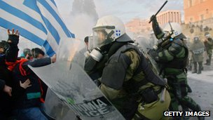 People clash with police in the streets during a demonstration against the new austerity measures in Athens on February 12