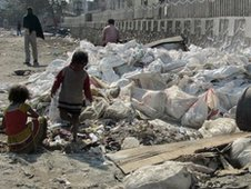 Children sift through rubbish in north Delhi slum