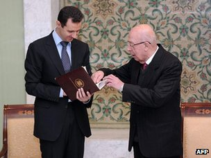 Bashar al-Assad is presented with a copy of the draft constitution by Mazhar al-Anbari (12 February 2012)