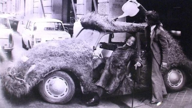 A photograph of Dali in a car covered in grass