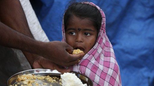 Child being fed by her father in India