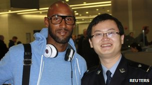 French soccer player Nicolas Anelka of Shanghai Shenhua poses with a Chinese immigration officer at Shanghai Pudong airport 15 February 2012