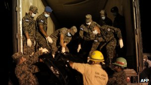 Soldiers help remove the corpses from the scene at the prison in Comayagua