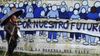 "A man walks past a graffiti which reads ""Fight for our future"" in Turon, northern Spain"