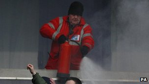 A steward puts out a flare in the stands during the match at the Reebok Stadium
