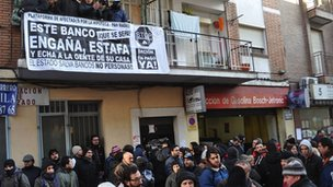 Protesters fill a Madrid street beneath a balcony displaying a banner